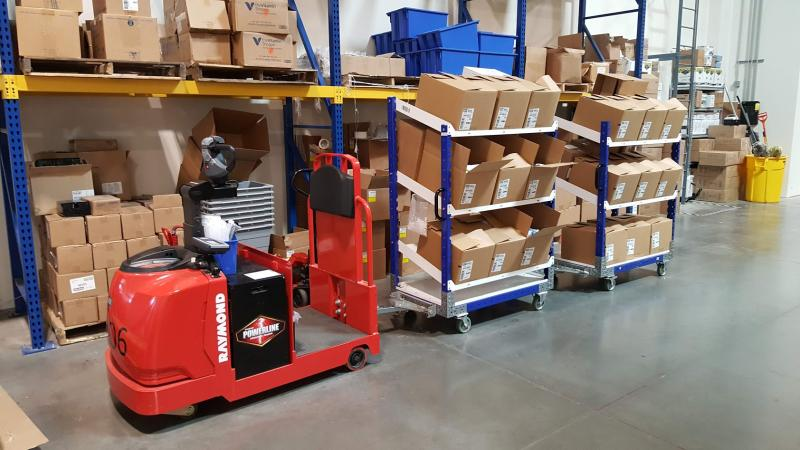 FlexQube Material Handling flow shelf carts connected to a tugger