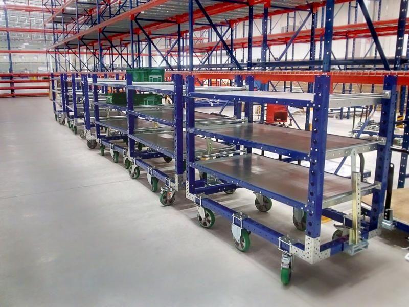 FlexQube flat shelf tugger carts in a tugger train